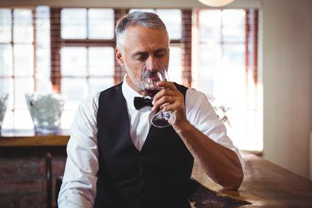 bar counter: Bartender sitting at bar counter drinking wine Stock Photo