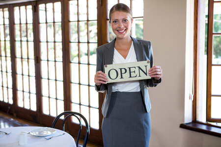 table skirt: Woman holding a sign with open in a restaurant