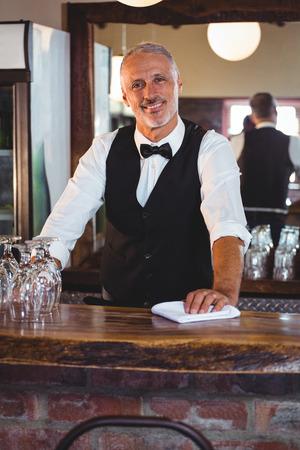 bartending: Portrait of smiling bartender cleaning bar counter