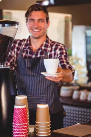 handing over: Waiter handing over a coffee in a cafe Stock Photo