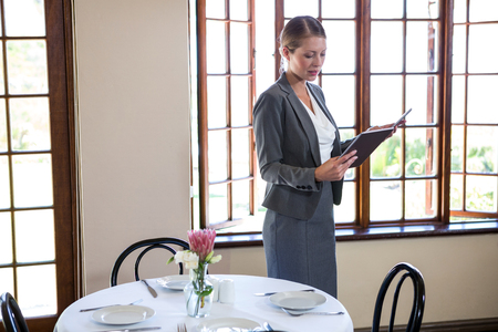 table skirt: Woman holding a clipboard in a restaurant