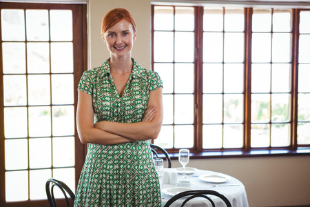 Woman standing with arms crossed in a restaurant Stock Photo