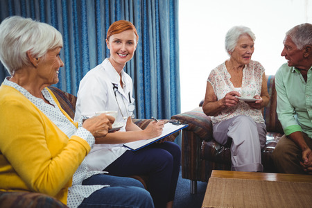 sheltered accommodation: Smiling nurse looking at camera in the middle of senior persons Stock Photo