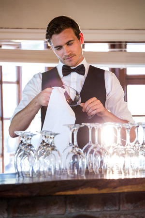 bar counter: Bartender cleaning wine glass at bar counter