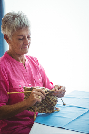 sheltered accommodation: Retired concentrate woman doing some knitting