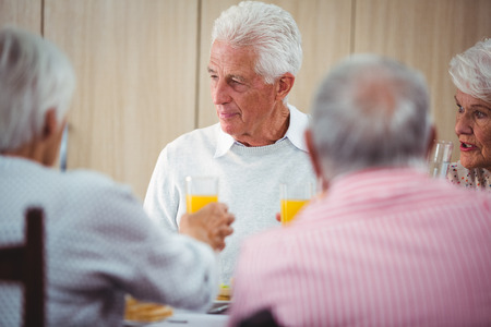 sheltered accommodation: Senior people having an orange juice drink during the lunch Stock Photo