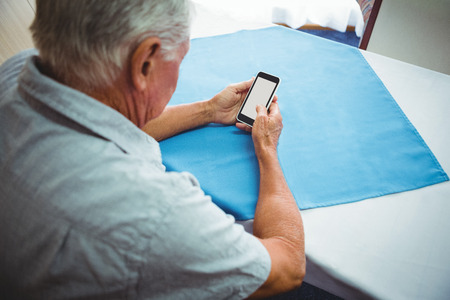 common room: Seated retired man looking at his smartphone in retirement home