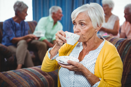 sheltered accommodation: Senior woman drinking a cup of coffee looking away Stock Photo