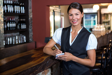 order in: Portrait of smiling waitress taking order in restaurant