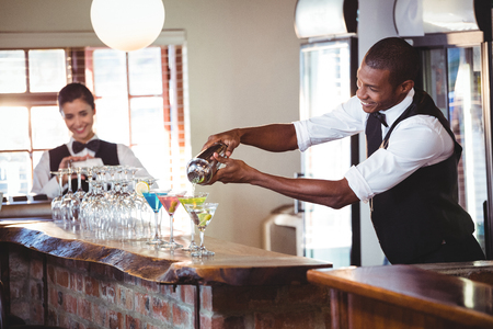 drinks on bar: Bartender pouring a drink from a shaker to a glass on bar counter in bar Stock Photo