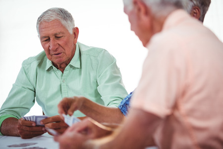 sheltered accommodation: Smiling seniors people playing cards in a retirement home Stock Photo