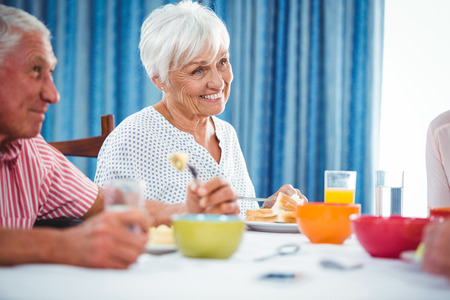 sheltered accommodation: Senior smiling woman during breakfast in a retirement home