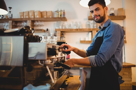 espresso machine: Portrait of young man taking coffee from espresso machine at office cafeteria