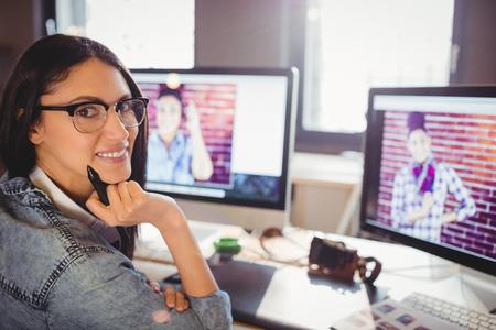 stylus: Portrait of happy female graphic designer holding stylus at office