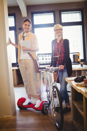 hover: Graphic designer holding bicycle while colleague standing on hover board in office