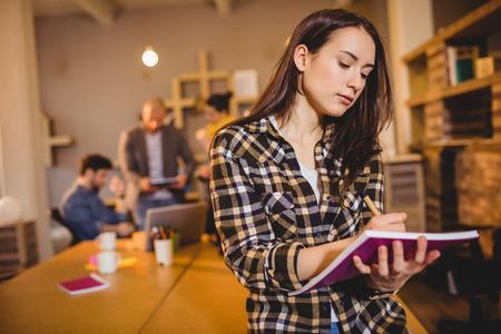 competencias laborales: diseñador gráfico que hace notas en su diario en la oficina