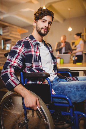 designer chair: Portrait of graphic designer sitting on a wheel chair while colleagues interacting in background