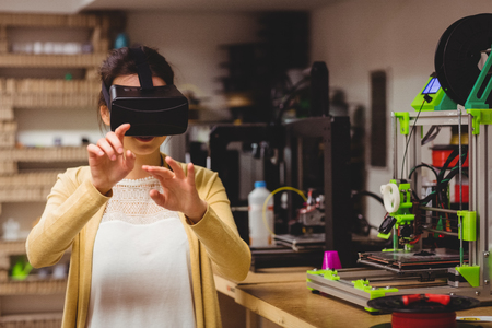 virtual office: Female graphic designer using the virtual reality headset at office