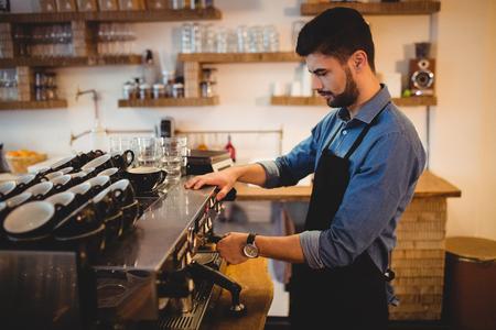 espresso machine: Man taking coffee from espresso machine in office cafeteria
