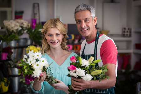 florists: Portrait of smiling florists holding bunch of flowers in flower shop