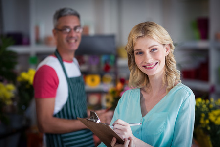 noting: Portrait of smiling female florist noting on clipboard at flower shop Stock Photo