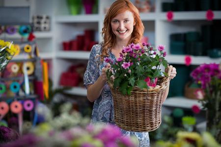 wicker work: Portrait of happy female florist holding basket of flowers in the shop