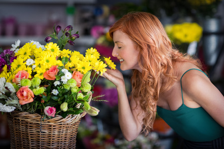 wicker work: Smiling female florist smelling flowers at flower shop