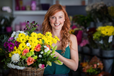 wicker work: Portrait of happy female florist holding basket of flowers in the shop