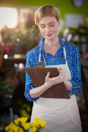 noting: Female florist noting on clipboard at flower shop Stock Photo