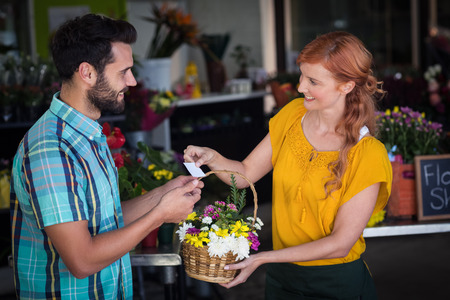 visiting card: Female florist giving visiting card and flower basket to customer in the flower shop