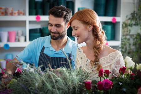 arranging: Happy couple arranging flowers in the flower shop Stock Photo