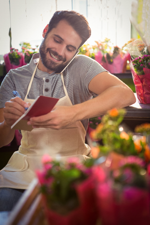 noting: Male florist noting order in dairy while talking on mobile phone at his flower shop