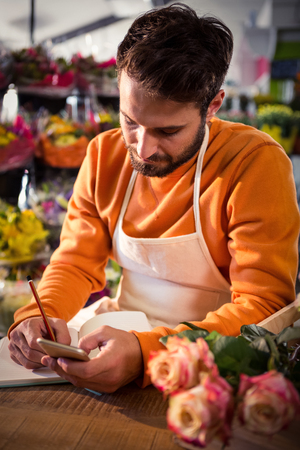 noting: Male florist noting order in dairy from mobile phone Stock Photo