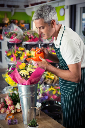 wicker work: Male florist watering flowers with watering can at his flower shop