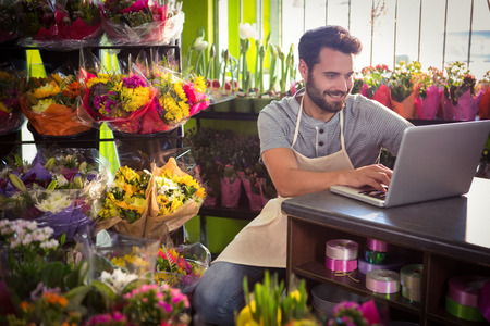 Male florist using laptop at his flower shop Reklamní fotografie