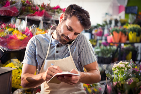 noting: Male florist noting order in diary while talking on mobile phone at his flower shop