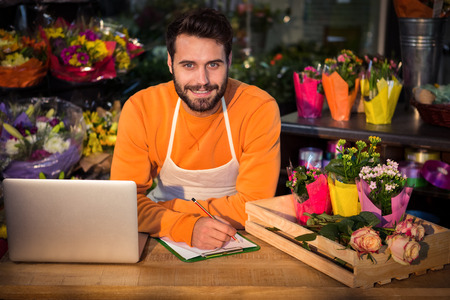 noting: Portrait of male florist noting order in notepad at his flower shop Stock Photo