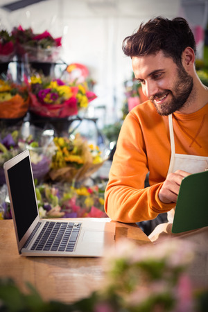 order in: Male florist checking order in laptop at his flower shop