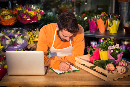 noting: Male florist noting order in notepad at his flower shop Stock Photo