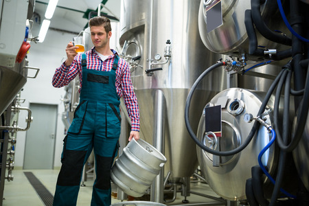 brewery: Brewery holding keg and testing beer at brewery factory Stock Photo
