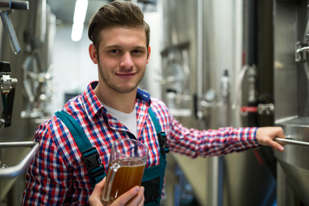 brewer: Brewer holding pint of beer at brewery factory Stock Photo
