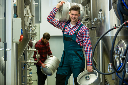 brewers: Portrait of brewers carrying keg at brewery factory Stock Photo