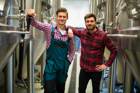 brewers: Portrait of brewers with arms crossed at brewery