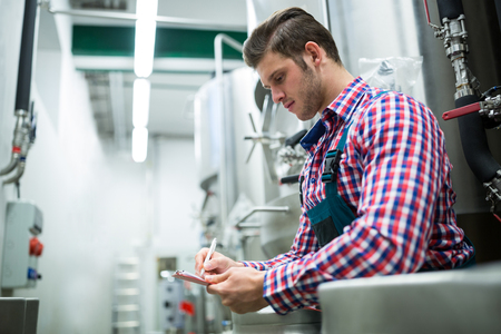 brewery: Maintenance worker writing on clipboard at brewery Stock Photo