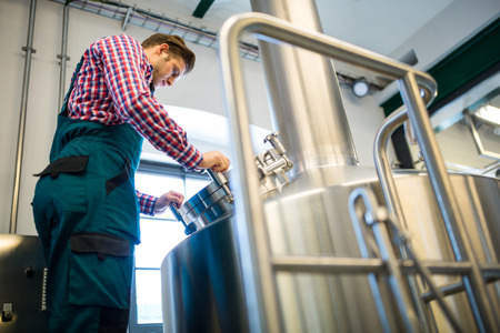 brewery: Attentive maintenance worker working at brewery