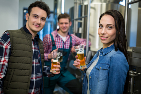 brewers: Portrait of brewers holding beer glasses at brewery factory