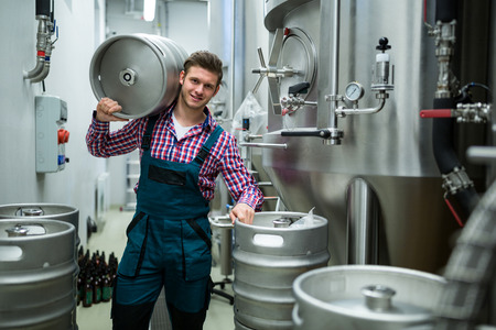 brewers: Portrait of brewers carrying keg on shoulder at brewery factory Stock Photo