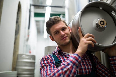 brewer: Portrait of happy brewer carrying keg at brewery factory