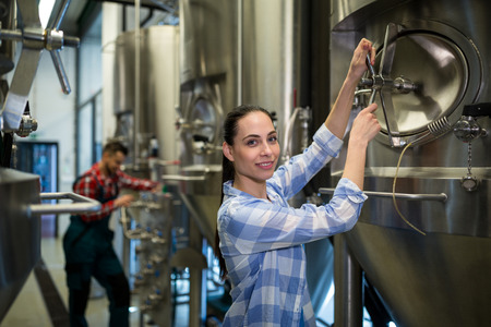 brewery: Portrait of female maintenance worker examining brewery machine at brewery