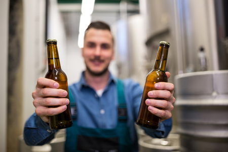 microbrewery: Brewer holding two beer bottle at brewery Stock Photo
